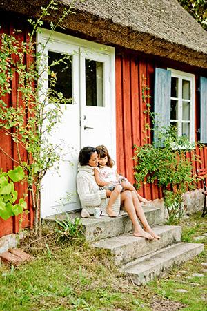 Mutter mit Kind vor ihrem Ferienhaus in Schweden